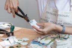 Lieu de travail du maître de mosaïque : le ` s de femmes remet l'outil de fixation pour des détails de mosaïque en cours de faire Images stock