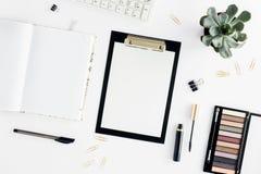 Lieu de travail féminin avec le presse-papiers, fard à paupières, mascara, clavier Images stock