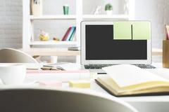 Lieu de travail lumineux avec l'écran blanc d'ordinateur portable Photos stock