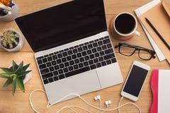 Lieu de travail masculin avec l'ordinateur portable et le smartphone Photographie stock