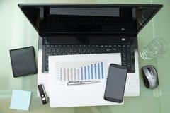 Lieu de travail moderne avec l'ordinateur portable et les accessoires sur le bureau en verre Photos stock
