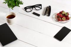Lieu de travail moderne avec la tablette numérique et le téléphone portable, la tasse de café et la fleur sur le fond blanc Vue s Images stock