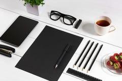 Lieu de travail moderne avec la tablette numérique et le téléphone portable, la tasse de café, le stylo et la feuille de papier v Photos stock