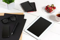 Lieu de travail moderne avec la tablette numérique et le téléphone portable, la tasse de café, le stylo et la feuille de papier v Photographie stock