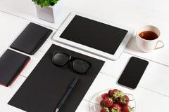 Lieu de travail moderne avec la tablette numérique et le téléphone portable, la tasse de café, le stylo et la feuille de papier v Images stock