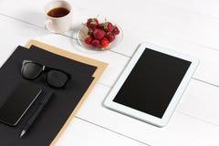 Lieu de travail moderne avec la tablette numérique et le téléphone portable, la tasse de café, le stylo et la feuille de papier v Photo stock