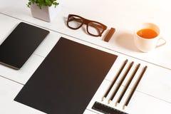 Lieu de travail moderne avec la tablette numérique et le téléphone portable, la tasse de café, le stylo et la feuille de papier v Image libre de droits