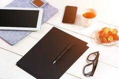 Lieu de travail moderne avec la tablette numérique et le téléphone portable, la tasse de café, le stylo et la feuille de papier v Image stock
