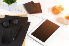 Lieu de travail moderne avec la tablette numérique et le téléphone portable, la tasse de café, le stylo et la feuille de papier v Photographie stock libre de droits