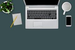 Lieu de travail moderne avec le calculateur numérique, téléphone portable, tasse, fiche de travail vide avec le crayon, plante ve Photographie stock libre de droits