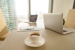 Lieu de travail moderne de bureau, tasse de café, ordinateurs portables sur le negot de conférence Image libre de droits