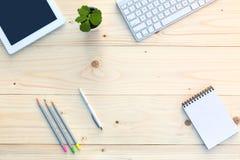 Lieu de travail sur le bureau en bois léger avec l'électronique et la fleur de papeterie photo stock