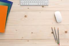 Lieu de travail sur le bureau en bois léger avec la papeterie et l'électronique images libres de droits