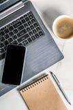 Lieu de travail, table blanche de bureau avec l'ordinateur portable, smartphone, tasse de café Photo libre de droits