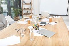 lieu de travail vide d'affaires avec les tasses jetables, les dispositifs numériques et les papiers image stock