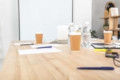 lieu de travail vide d'affaires avec les tasses jetables, les dispositifs numériques et les papiers image libre de droits