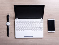Lieu de travail - vue supérieure de l'ordinateur portable blanc, du téléphone intelligent et de la montre sur t Images libres de droits