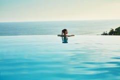 Lieu de villégiature luxueux Femme détendant dans la piscine Vacances de voyage d'été Photographie stock libre de droits
