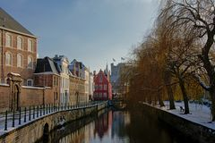 Lieve canal on a winter day with snow in Ghent, belgium. Lieve canal with historical buildings and weeping willows on the quay, and the tower of the medieval royalty free stock photo