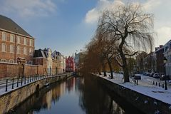 Lieve canal on a winter day with snow in Ghent, belgium. Lieve canal with historical buildings and weeping willows on the quay, and the tower of the medieval stock image