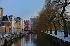 Lieve canal on a winter day with snow in Ghent, belgium. Lieve canal with historical buildings and weeping willows on the quay, and the tower of the medieval royalty free stock image