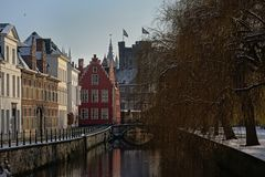 Lieve canal on a winter day with snow in Ghent, belgium. Lieve canal with historical buildings and weeping willows on the quay, and the tower of the medieval stock images