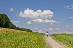 Life. Child walking along a path in the countryside slightly uphill and towards a blue sky, symbolizing the path of life Stock Photo
