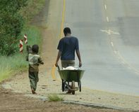 Life in Africa. Two boys with a wheelbarrow are walking on a road Stock Image