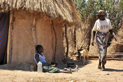Life in african village. African family in village next to their hut, typical landscape of day to day life Stock Photo