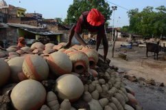 Daily life. Allahabad: A potter put the earthen pitcher on a bhatti for the finalizing to sell in the market in Allahabad on 11-05-2015. Earthen pitcher is used Stock Image