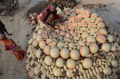 Daily life. Allahabad: A potter put the earthen pitcher on a bhatti for the finalizing to sell in the market in Allahabad on 11-05-2015. Earthen pitcher is used Stock Photo