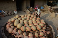 Daily life. Allahabad: A potter put the earthen pitcher on a bhatti for the finalizing to sell in the market in Allahabad on 11-05-2015. Earthen pitcher is used Royalty Free Stock Image