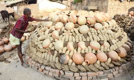 Daily life. Allahabad: A potter put the earthen pitcher on a bhatti for the finalizing to sell in the market in Allahabad on 11-05-2015. Earthen pitcher is used Royalty Free Stock Photos