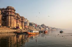Life along the Ganges Ganga River.Pilgrims bath and pray, peop. Le walk,washes and dry laundry.Tourists take boat to sea old temples and ghats from the river royalty free stock image