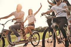 Life is awesome!. Two young modern women giving each other high five while cycling with friends outdoors Stock Image