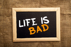 Life is bad. Negative message on black board Royalty Free Stock Images