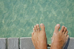 Life is a Beach (Feet). One of a large series. Man's feet on the edge of a wooden jetty with tropical water below Royalty Free Stock Photography