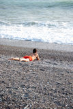 Life is beautiful. A young man sunbathing and gazing the waves on a beach of stones Stock Image