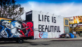 Life Is Beautiful Mural In Los Angeles. Driving in Los Angeles reveals 'Life Is Beautiful' mural landscape on La Brea Boulevard with a homeless campsite on the Stock Photos