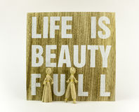 Life is beautifull. Wooden board with message and paper dolls Royalty Free Stock Photography