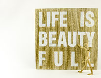 Life is beautifull. Wooden board with message and wooden doll Royalty Free Stock Photo