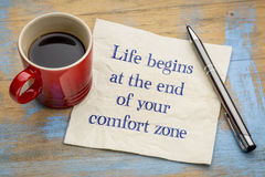 Life begins at the end of comfort zone. Life begins at the end of your comfort zone - inspirational handwriting on a napkin with a cup of coffee royalty free stock photography