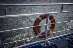 A life belt on a boat. A red life belt on a blue boat royalty free stock photo