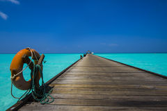 Life belt at the jetty. Life belt on a wooden jetty leading to the horizon stock image