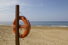 Life belt on the beach in ampulia Italy. Life belt with ocean view on a beach in ampulia Italy royalty free stock photography