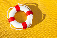 Life belt. Red and white colored life belt in front of a yellow background stock image