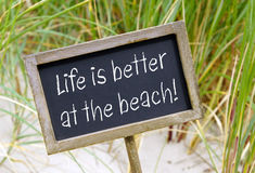 Life is better at the Beach. Chalkboard with text and beach in the background stock photos