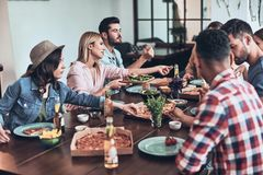 Life is better with friends. Group of young people in casual clothing eating and smiling while having a dinner party indoors royalty free stock photo