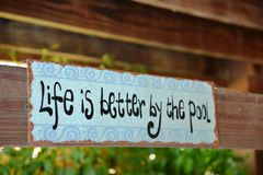 Life is Better By The Pool. Sign affixed to the overhanging board on a swing by a swimming pool Stock Photography