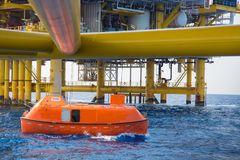Life boat or survival craft while annual testing to escape at oil and gas central processing platform. Life boat or survival craft while annual testing to Stock Image